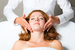 Wellness - woman getting head massage in Spa. Wellness - woman getting massage in Spa, it is a massage for the head or face Stock Image