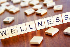 Wellness word on block concept, letters placed on a desk in prec Stock Photography
