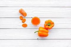 Wellnessbeståndsdelar Den orange detoxen dricker med paprica och moroten på bästa sikt för vit träbakgrund Royaltyfria Bilder