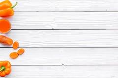 Wellnessbeståndsdelar Den orange detoxen dricker med paprica och moroten på vit träcopyspace för den bästa sikten för bakgrund Arkivfoto