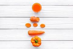 Wellnessbeståndsdelar Den orange detoxen dricker med paprica och moroten på vit träcopyspace för den bästa sikten för bakgrund Royaltyfria Foton
