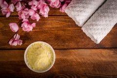 Wellnesseinstellung Seesalz in der Schüssel, im Tuch und in den Blumen auf braunem t Stockfotografie