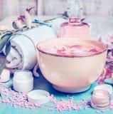 Wellnessinställningen med orkidén blommar att sväva i bunke av vatten med brunnsort- och skönhetsmedelhjälpmedel Royaltyfria Foton