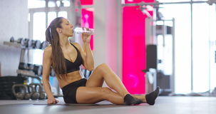 Welltrained resting fitness woman sitting on the floor drinking water stock video footage