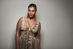 Wellustig vrouwelijk model die een mooie kleding stellen royalty-vrije stock afbeeldingen