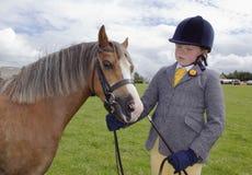 Wels meisje bij dressuurproef in bouwvakker met poney Royalty-vrije Stock Foto