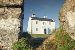 Welsh Coastal House in Bright Morning Light. Historic coastal white house seeing through old eroded cliffs of Penmon beach in North Wales, UK Stock Photography