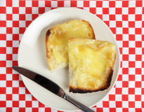 Welsh rabbit high angle with knife. A Welsh rabbit, or Welsh rarebit - a mix of cheddar cheese and egg with mustard, pepper and salt on toast. A traditional Stock Photos