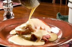 Welsh rarebit (Welsh rabbit). Velvety Welsh rarebit (Welsh rabbit) sauce - made with beer -pouring over toast, ham, eggs, and grilled tomatoes Royalty Free Stock Image