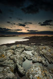Welsh Seascape. Sunset seascape from Trearddur Bay on the island of Anglesey in North Wales. The sky is reflected in the rock pools and the jagged rock that royalty free stock photos