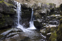 Welsh waterfall. A small Welsh waterfall and water pool surrounded by wet and slippery moss and algae covered rocks stock photo