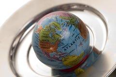 Welt auf einer silbernen Mehrlagenplatte Stockfotos