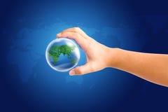 Welt in der Hand und globales auf blauem Kartenhintergrund Stockbild