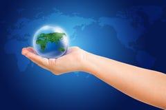 Welt in der Hand und globales auf blauem Kartenhintergrund Stockfotografie