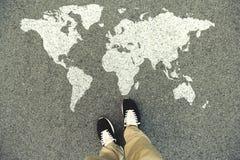 Weltkarte auf einer Asphaltstraße Draufsicht der Beine und der Schuhe Lizenzfreie Stockbilder