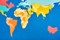 Weltkarte herausgeschnitten von Papier gefärbt auf Blau Stockfoto