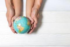Weltkonzept: Zwei menschliche Hände halten global auf hölzernem backgrou stockbild