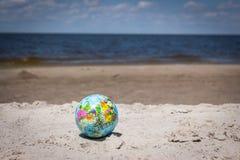Weltkugel-Wasserball, der auf Strand durch den Ozean liegt Stockbild