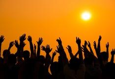 Weltleute, die während des Sonnenuntergangs feiern Stockbild