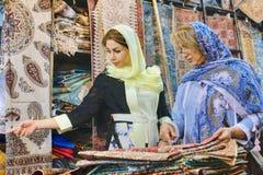 Weltliche iranische Frauen wählen Waren für Kauf im Teppichspeicher Lizenzfreie Stockfotografie