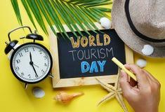 Welttourismus-Tagestypographie Hand, die gelbe Kreide und Blac hält Stockbilder