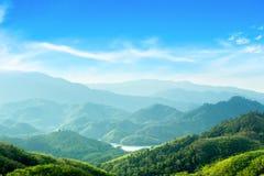 Weltumwelttagkonzept: Gr?ne Berge und sch?ne Himmelwolken unter dem blauen Himmel stockbild