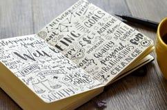 WELZIJN hand-van letters voorzien schetsnota's over notitieboekje met koffie en pen stock foto's