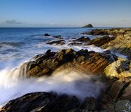 Wembury coastline. Dawn at Wembury Beach South West Devon with the sea swirling around the exposed rocks and the Mew Stone on the horizon royalty free stock photography