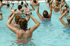 Wemen doing water aerobic. People are doing aerobic in pool Stock Photos