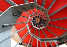 Wendeltreppe mit rotem Teppich in einem modernen Gebäude Stockbilder