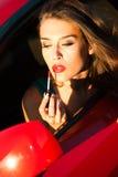 Wenden Sie Lippenstift im Auto an Lizenzfreie Stockbilder