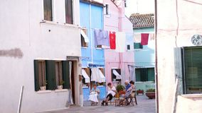 WENECJA, BURANO WŁOCHY, LIPIEC, - 7, 2018: atmosferyczna ulica na wyspie Burano Starzy ludzie siedzą na ulicie, haftują zbiory wideo