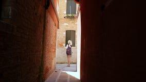 WENECJA WŁOCHY, LIPIEC, - 7, 2018: przy końcówką bardzo wąska ulica w Wenecja, młoda kobieta turyście z a i kapeluszem, zbiory
