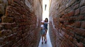 WENECJA WŁOCHY, LIPIEC, - 7, 2018: wzdłuż bardzo wąskiej ulicy Wenecja, między starymi domami, nastolatek dziewczyną, dzieckiem i zbiory wideo