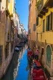 WENECJA WŁOCHY, Maj, - 23, 2016: Gondolier bierze opiekę dwa zakotwiczał gondole w Wenecja kanale z jasnym niebem Obraz Stock
