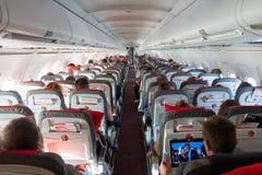 WENEN, OOSTENRIJK - SEPTEMBER 02, 2017: Passagierscabine tijdens de vlucht met mensen, mens die op een film op laptop letten Royalty-vrije Stock Foto