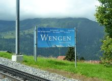Wengen. Sign board, rail to Jungfrau, cloudy and forest mountain, building roofs Stock Image