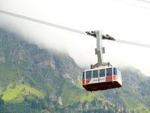 Wengen, Svizzera 08/04/2009 Cabina di funivia che va su alla montagna fotografia stock