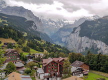 Wengen in the swiss Alps. Wengen  in the swiss Alps, in a valley with rural houses, in the background are mountains on a cloudy day Stock Image