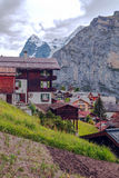 Wengen in the swiss Alps. Wengen  in the swiss Alps, in a valley with rural houses, in the background are mountains  on a cloudy day.It´s a vertical picture Royalty Free Stock Photo