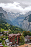 Wengen in the swiss Alps. Wengen  in the swiss Alps, in a valley with rural houses, in the background are mountains with snow on a cloudy day.It´s a vertical Stock Photo