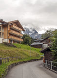 Wengen in the swiss Alps. Wengen  in the swiss Alps, in a valley with rural houses, in the background are mountains with snow on a cloudy day.It´s a vertical Royalty Free Stock Image