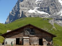 A mountain hut and the Swiss Alps in the background stock photo