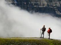 Wengen, Zwitserland 08/17/2010 Twee wandelaars in het hooggebergte bewonderen het landschap royalty-vrije stock afbeelding