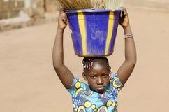Wenig afrikanisches ethnisches Schulmädchen, das Wanne auf ihrem kopf- Wom hält stockfotos