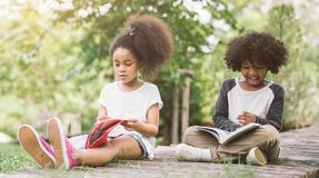 Wenig Afrokindermädchen-Lesebuch zwischen Grün nagelt Wiesengarten mit Freund fest lizenzfreie stockfotografie
