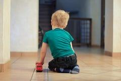 Wenig allein kaukasisches Baby mit dem angemessenen Haar sitzt auf dem Boden, zurück zu dem Zuschauer, mit rotem Busspielzeug Ein stockfotos