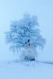 Wenig alte Kapelle und Od-Baum mit Raureif und snoow, nebeliger Weihnachtstag nahe der Straße während des Winters Lizenzfreie Stockfotos