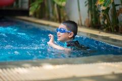 Wenig asiatische arabische Jungenschwimmen der Mischung Tätigkeit des Swimmingpools an der im Freien lizenzfreies stockbild