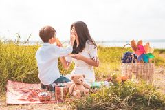 Wenig asiatischer Junge sein Fütterungsimbiß der Mutter in der Wiese, wenn Picknick getan wird Mutter und Sohn, die zusammen spie stockfotos
